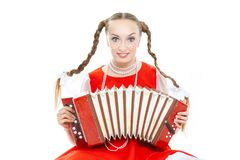 Pretty young cheerful woman  with ridiculous  plaits in russian folk costume plays an accordion. Pretty young cheerful woman with ridiculous plaits in russian royalty free stock images