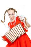 Pretty young cheerful woman  with ridiculous  plaits in russian folk costume. With plays an accordion at white background, isolated stock photo