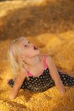 Young Child in Fall Harvest Corn. Pretty Young Child Playing in fall harvest Corn Pile Stock Photography