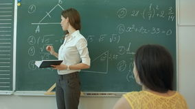 Pretty young college student by the chalkboard or blackboard during a math class stock video footage