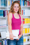 Pretty, young college student female  student in a library Royalty Free Stock Photography