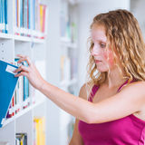 Pretty, young college student female  student in a library Royalty Free Stock Image