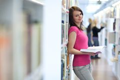 Pretty young college student in a library. (shallow DOF; color toned image Royalty Free Stock Photos