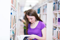 Pretty, young college student in a library Royalty Free Stock Photos