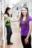Pretty, young college student in a library Royalty Free Stock Image