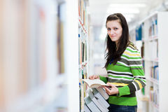 Pretty, young college student in a library. (shallow DOF; color toned image Stock Image
