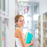 Pretty young college student in a library Royalty Free Stock Photography
