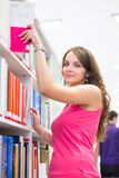 Pretty young college student in a library Royalty Free Stock Photos
