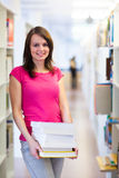 Pretty young college student in a library stock photo