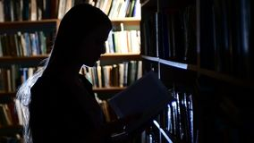 Pretty young college student in a library, chooses stock footage