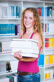 Pretty, young college student  in a library Stock Photos