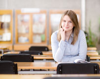 Pretty young college student in a library. Stock Photos