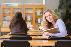 Pretty young college student in a library. looking at camera Royalty Free Stock Photos