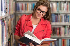 Pretty Young College Student In A Library Royalty Free Stock Photo