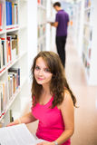 Pretty young college student in a library Stock Photography