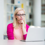 Pretty young college student in a library. Shallow DOF; color toned image Royalty Free Stock Photo
