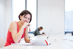 Pretty young college student studying in the library Royalty Free Stock Photography