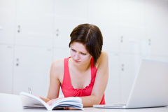 Pretty young college student studying in the library Stock Image