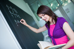 Pretty, young college student writing on the chalkboard/blackboa Royalty Free Stock Image