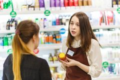 Pretty young consultant holds consultation to the buyer in cosmetic shop. Pretty young consultant holds new goodsto the buyer in cosmetic shop royalty free stock images
