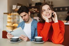 Pretty young couple sitting at a cafe table together Stock Photo
