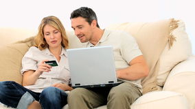 Pretty young couple using a credit card on internet Royalty Free Stock Photography
