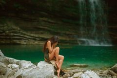 Pretty young crying girl with dark black long hair sitting alone in lagoon of Martvili Canyon, lady in long green cut. Dress and bare legs covered her face with royalty free stock photography