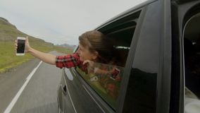 Young girl makes selfie out of car window stock footage