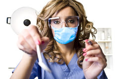 Pretty young dentist. A young pretty dentist with tools getting ready to take a look Stock Photography
