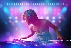 Disc jockey mixing music on turntables on stage with lights and stroboscopes. Pretty young disc jockey mixing music on turntables on stage with lights and stock photography