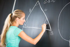 Pretty young elementary school/college teacher. Writing on the chalkboard/blackboa rd during a math class (color toned image; shallow DOF royalty free stock image