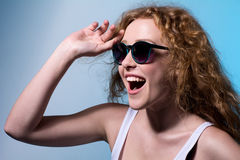 Pretty young emotional girl in sunglasses looking to the side Stock Photos