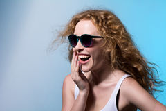 Pretty young emotional girl in sunglasses looking to the side Stock Image
