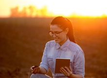 Woman with tablet and soil in hands. Pretty young engineer woman holding dirt in hand and tablet. Researching soil in field stock image
