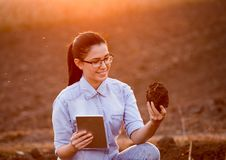 Woman with tablet and earth clod Royalty Free Stock Photos