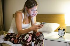 Pretty young exhausted woman suffering insomnia using her mobile phone while sitting on bed in the bedroom at home. Shot of pretty young woman suffering stock photo