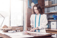 Pretty young fashion designer cutting cloth using scissors while working in studio Royalty Free Stock Image