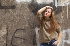 Pretty young fashion girl standing near a stone wall Royalty Free Stock Image