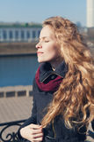 Pretty young fashion woman with long curly hair enjoying the spring sun with eyes closed near the river Stock Photos