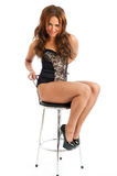 Pretty young female against white on stool Royalty Free Stock Images