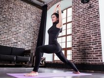 Pretty young female athlete in black sports outfit doing lunge exercise or standing in yoga low warrior pose on mat at stock image