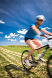 Pretty, young female biker outdoors on her mountain bike Royalty Free Stock Images