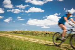 Pretty, young female biker outdoors on her mountain bike Stock Image
