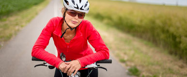 Pretty, young female biker outdoors on her mountain bike Stock Images