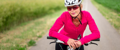 Pretty, young female biker outdoors on her mountain bike Royalty Free Stock Photos
