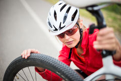 Pretty, young female biker outdoors on her mountain bike Royalty Free Stock Photo