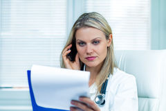 Pretty Young Female Doctor Is Consulting Medical Results. By Her Cell Phone Stock Photography