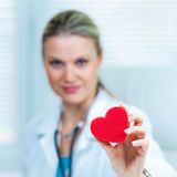 Pretty Young Female Doctor Is Showing a Red Heart. In Ambulance (shallow depth of field, color toned image royalty free stock image