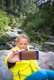 Pretty, young female hiker taking a selfie while outdoors Royalty Free Stock Images