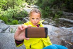 Pretty, young female hiker taking a selfie while outdoors Royalty Free Stock Photo